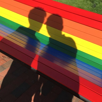 Silhouettes on a rainbow bench.