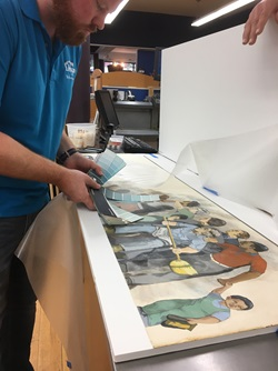 A conservator compares color samples with a printed copy of Bernard Lacasse's