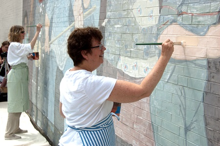 Conservator, Rika Smith-Mcnally, applies a fresh coat of paint to the mural