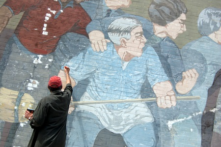 Mural artist, Bernard LaCasse, applies a fresh coat of blue paint to one of the protesters