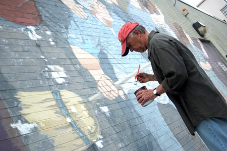 Mural artist, Bernard LaCasse, reapplies paint to his brush