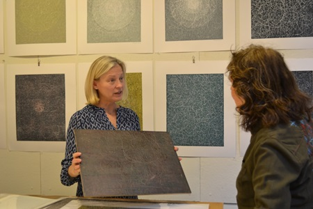 An artist speaks with an attendee at during Cambridge Open Studios.