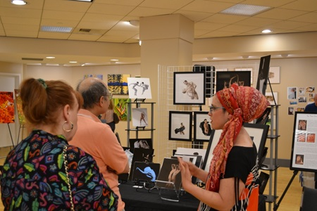 A vendor shows their work to viewers during Cambridge Open Studios.
