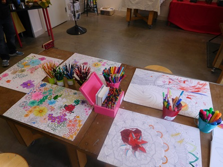A table with partially colored in coloring pages by Mireli Books