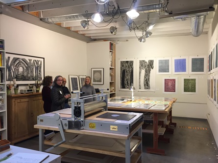 A group of artist talk in a printmaking studio in Cambridge