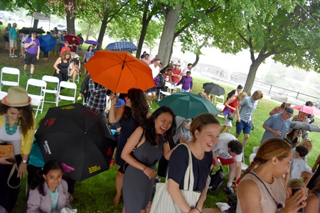 The crowd heads under the Dance Stage tent during a brief rain shower at the 2018 River Festival.