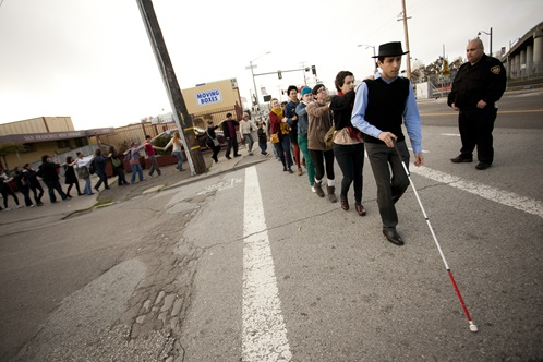 Carmen Papalia: Blind Field Shuttle - A line of people crossing the street with security guard