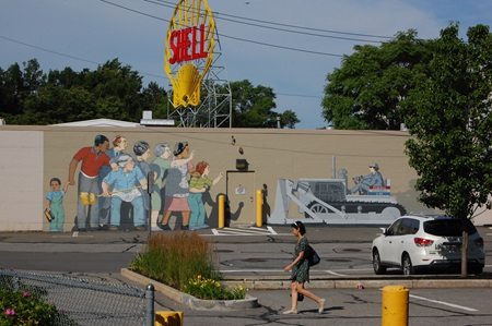 A far shot of the Beat the Belt mural featuring the Shell sign and a passerby walking