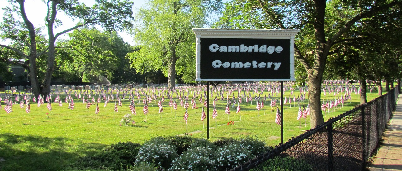 Cambridge Cemetery sign with american flags on each grave marker