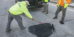 Photo of workers filling a pothole