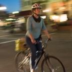 Smiling woman riding a bike at night