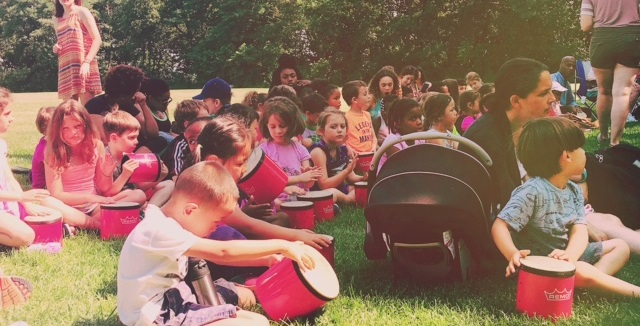 Children play bongo drums outdoors during a 2016 Summer in the City performance in Cambridge