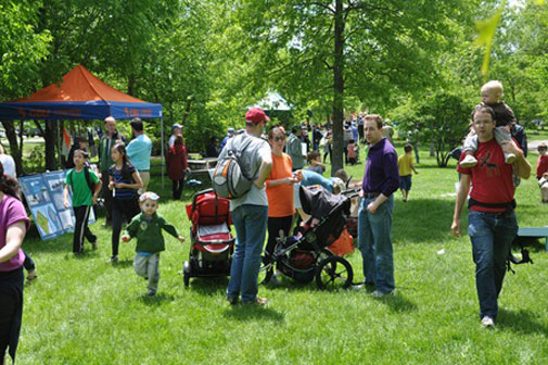 A grassy field with trees, in it are families looking at the info tables of Fresh Pond Day