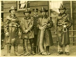 old time firefighters in gear holding equipment