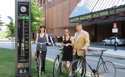 Three bicycle commuters stand next to the Eco-Totem on Broadway
