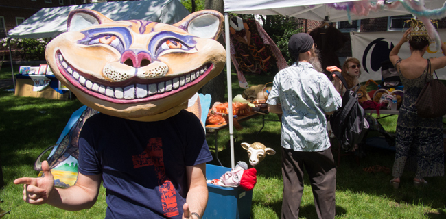 A visitor wears an oversized Cheshire Cat papier mache mask during Cambridge River Festival. In the background, others try on funky hats at one of the featured booths.