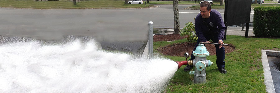 Firefighter opening a hydrant with water coming out