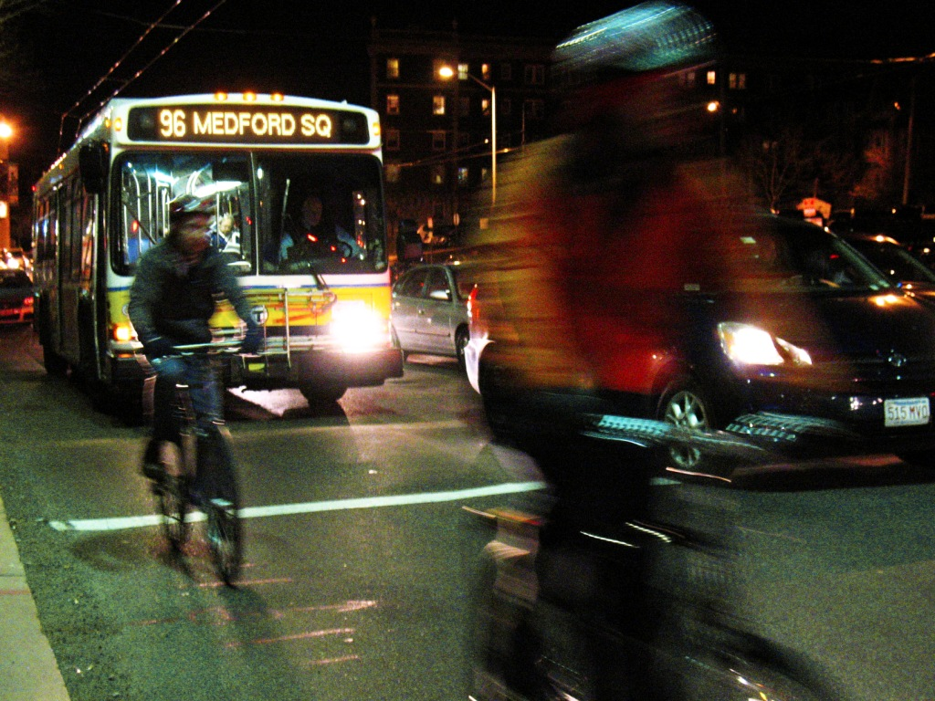 Bike riders and buses at night along Massachusetts Avenue