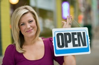 "Woman holding a small ""open"" sign"