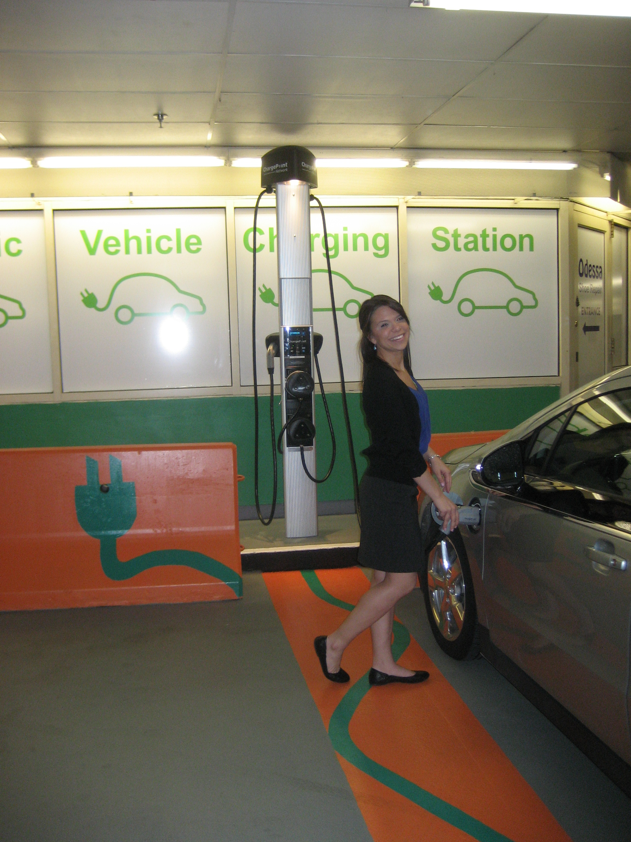 A woman charging an electric vehicle at the state-funded EV charging station in the Cambridgeside Galleria garage