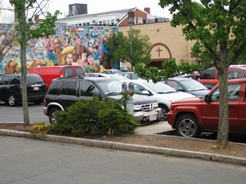 A colorful mural seen from a Central Square parking lot.