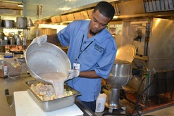 Cambridge Works participant preparing food at his job