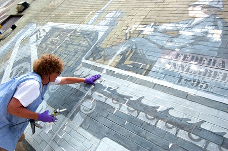 A conservator repairs cracks in the brick of the mural