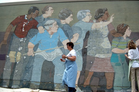 Rika McNally-Smith walks in front of the mural