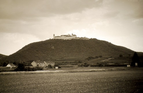 Sepia toned Image of a nunnery on a hill in the distance featured in the work of Andy Graydon