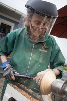 A craftswoman demonstrates her skills as a woodturner by carving a wooden bowl during Cambridge Open Studios.