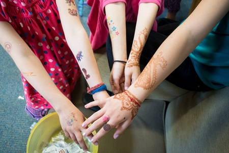 Girls show off their temporary henna designs and temporary tattoos during Cambridge Open Studios.