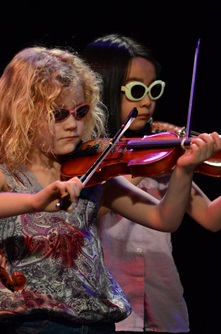 Young violinists perform together on stage wearing colorful sunglasses during Cambridge Open Studios.