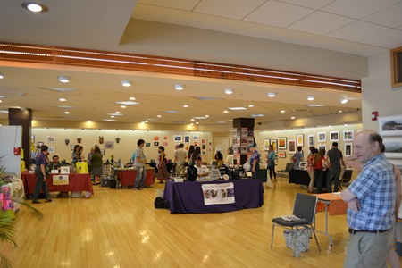 A large venue showcases many tables of artwork during Cambridge Open Studios.