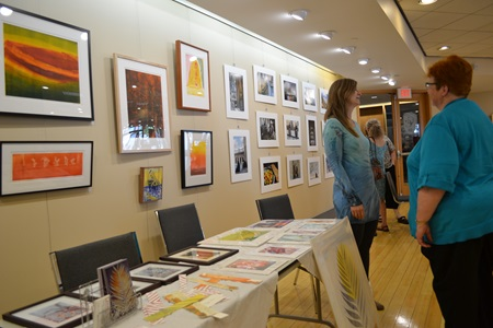 A viewer appreciates hanging print work at an artist table during Cambridge Open Studios.
