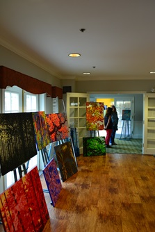 Several colorful paintings depicting trees from a participating artist during Cambridge Open Studios.