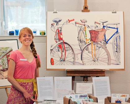An artist poses with her work at her vendor table during Cambridge Open Studios.