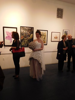 An artist modeling a sculptural dress piece at the Cambridge Arts Open Studios reception