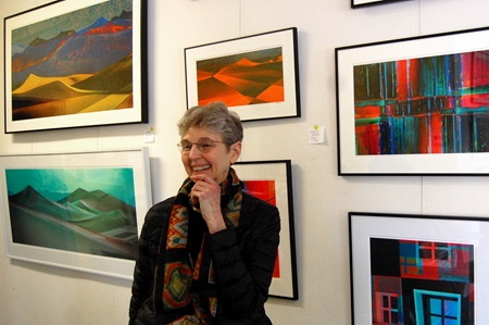 Artist Estelle Disch stands in front of some of her paintings