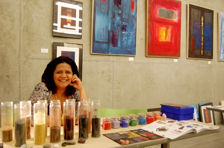 Cambridge Artist Margarette Mattos poses with some of her work