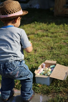 A young attendee investigates a box full of sidewalk chalk at River Festival
