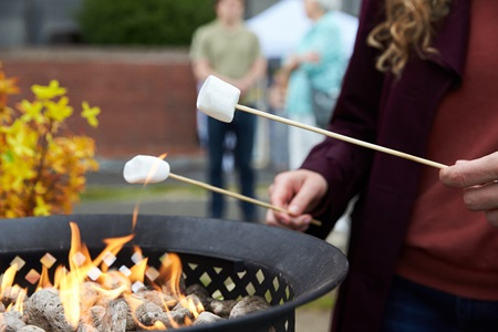 A couple toasts marshmallows over an open flame