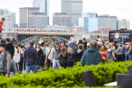 A crowd walking down the street with a view of the Boston skyline