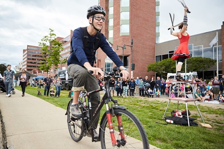 A young man rides by a performing artist on his bike