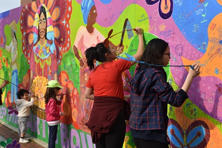 People add to Liz LaManche's interactive mural about women doing small scale farming at the 2019 Cambridge Arts River Festival.