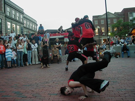 A breakdance crew performs for a public crowd in the middle of Harvard Square in Cambridge.