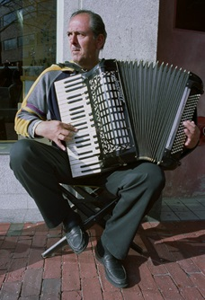 An accordion player performs on a street in Cambridge.