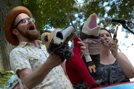 Red Yarn shows their two opossum puppets to the audience