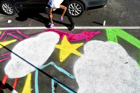 Lamar Atkins of Yurp Nation paints on the street during the Community Art Center's Port Arts Festival in Cambridge, June 15, 2018.