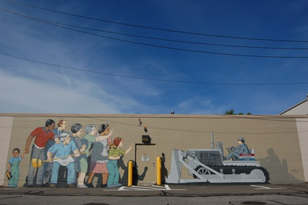 A show of the full stretch of the Beat the Belt mural on the side of the Microcenter building, fully repainted