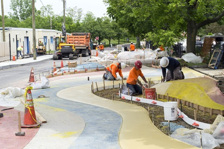 Workers laying down colorful concrete
